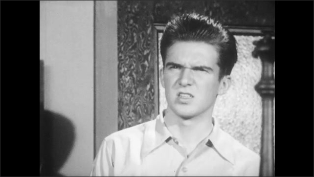 1950s: UNITED STATES: boys speak in classroom. Boys argue. Boy leaves classroom. Student talks to teacher