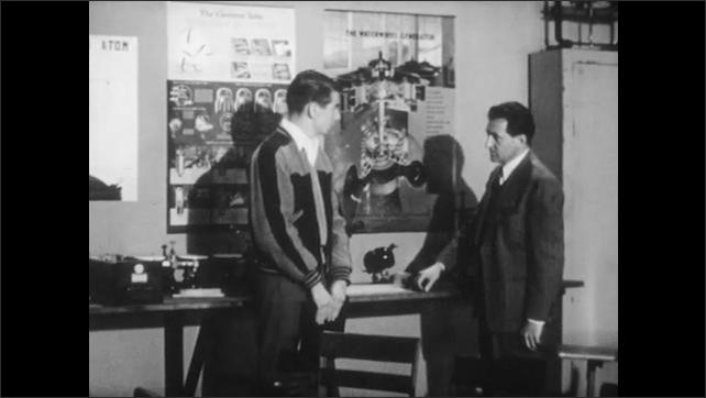 1950s: UNITED STATES: student talks to teacher. Man in physics classroom. Teacher gives advice to student. Teacher tidies class.