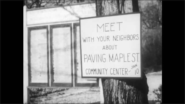 1950s: UNITED STATES: letter in newspaper. Meet with your neighbours poster on pole. Man arrives at meeting