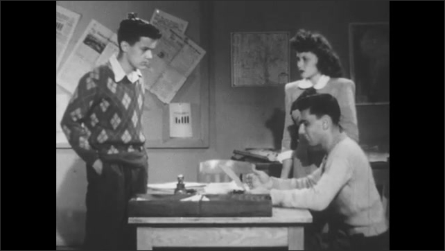 1950s: Young man in sweater stands at desk talking to man and woman on other side.