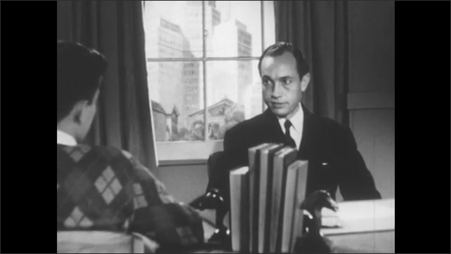 1950s: Young man is seated at desk talking to man sitting across from him.