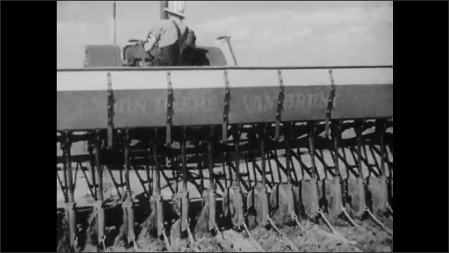 1950s: UNITED STATES: man fills feeder with grain. Man drives wide plough on field