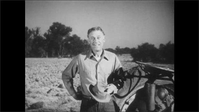 1950s: UNITED STATES: farmer wipes sweat from brow. Farmer climbs down from tractor. Farmer takes off hat. Farmer combs hair. Farmer puts on hat