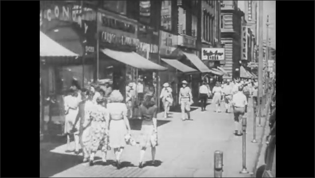 1950s: UNITED STATES: Farmer leans on gate. Lady in kitchen. People walk in city street. Shoppers in town. Man buys from lady at counter