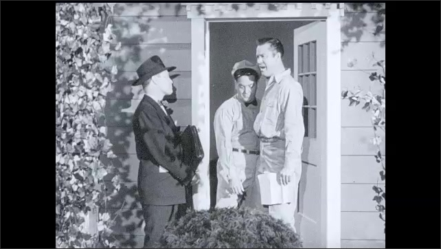 1950s: Man in suit and hat talks to man in doorway of house. Delivery driver leaves house. Woman in house approaches man in doorway and they all talk.