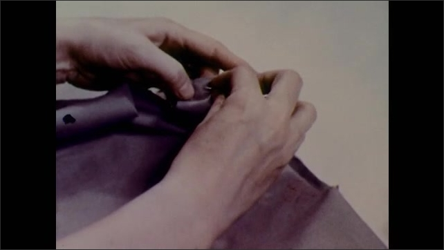1950s: Girl sews cuffs of dress. Girl points at neckline of dress.