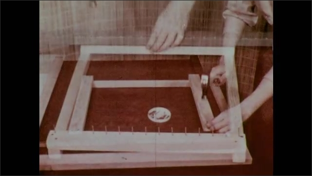 1950s: Hands construct a loom frame by nailing together wood lathe strips. Nails are pounded in a row on opposite sides of the frame.