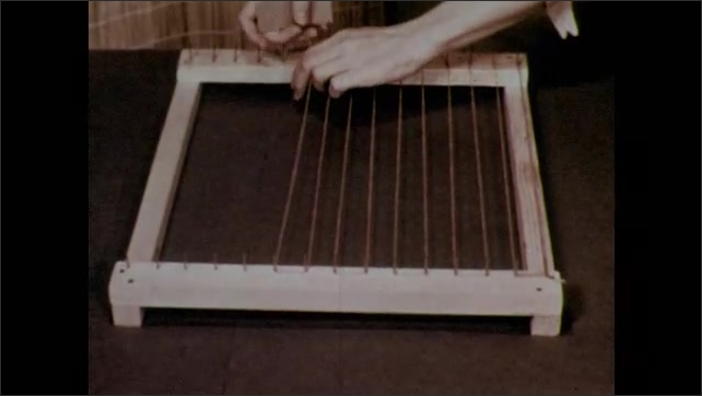 1950s: Hands hold up constructed loom. Strings are strung around the warp nails to make a grid. Ribbon is woven through the strings and tightened to the top.