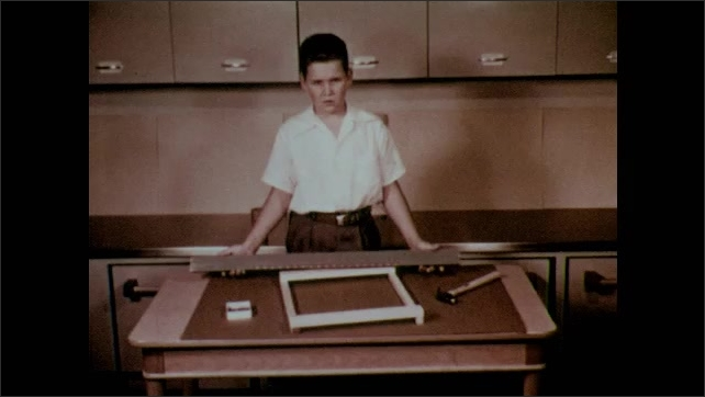 1950s: Boy points to nails along the topside and bottom of the loom frame. Boy holds up a measuring stick with holes to space out nailholes.