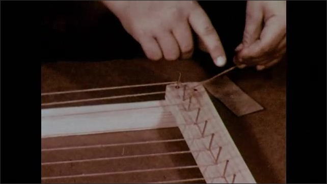 1950s: Boy ties warp string at the top and bottom of one set of nails and holds up the completed frame with warp string.