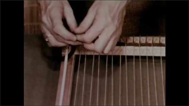 1950s: Two rods are placed parallal to each other on the loom to keep the sides from pulling in. Boy weaves around the rods. Hands feel the tension in the warp of the loom.