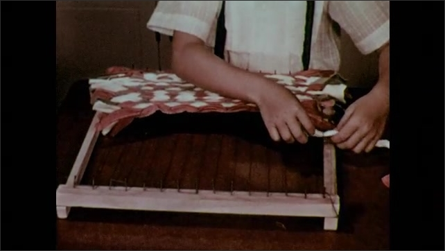 1950s: Boy weaves wide strips of fabric on loom, weaving over and under.