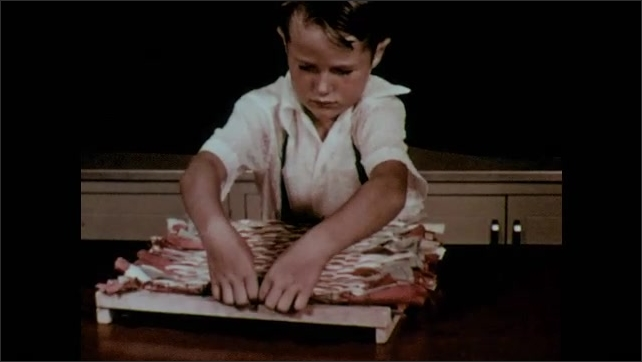 1950s: Boy removes weaving from loom.