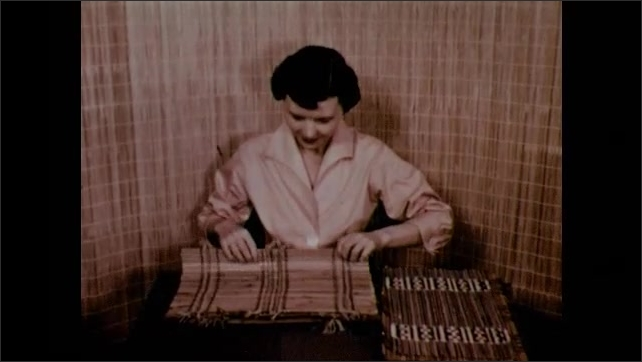 1950s: Woman shows different examples of bamboo weavings.