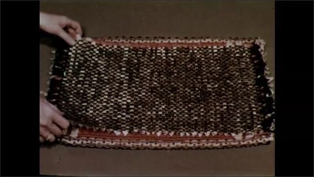 1950s: A pile of examples of small weavings. Hands remove individual weavings from the pile to show case the different styles and materials.