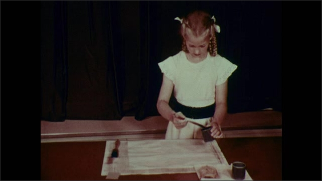 1950s: Girl brushes starched water over surface of paper on table. Girl drips paint over paper.