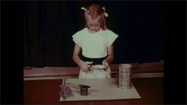 1950s: Girl turns tube with painting glued to it, over in her hands. Girl cuts excess off glued painting on lid of tube.