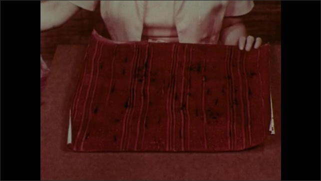 1950s: Woman goes through stack of finished starch paintings.