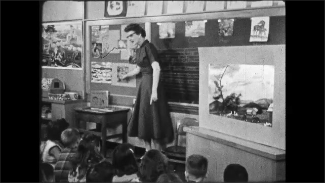 1950s: UNITED STATES: teacher shows first grade students a diorama in class. Elementary school teacher and students in classroom. Girl stands up in class.