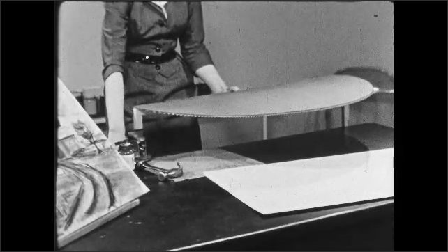 1950s: UNITED STATES: lady glues and nails base unit into position on diorama. Lady holds hammer. Teacher builds diorama in classroom.