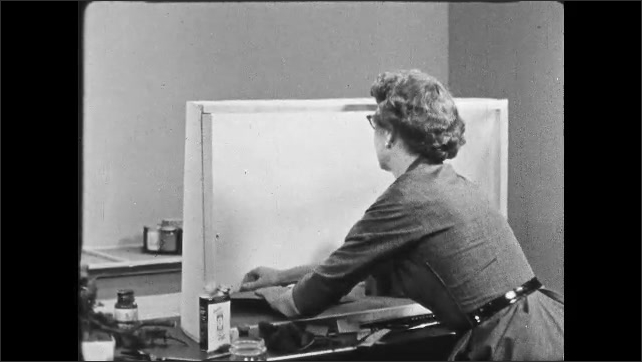 1950s: UNITED STATES: lady creates landscape for diorama. Lady builds diorama on table.