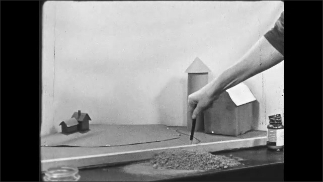 1950s: UNITED STATES: close up of lady's face as she concentrates. Lady marks base of diorama. Lady positions accessories in diorama