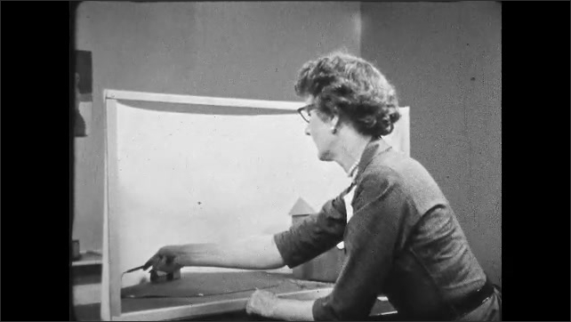 1950s: UNITED STATES: lady blocks off background on diorama. Lady works at desk. Lady with glasses concentrating.