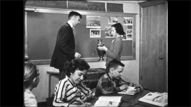1950s: UNITED STATES: girl researches in book in library. Student gives trophy to teacher. Man teaches students in class.