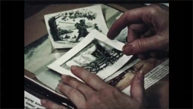 1940s: Woman at desk looks through folders of pictures.  Woman puts frame over image.