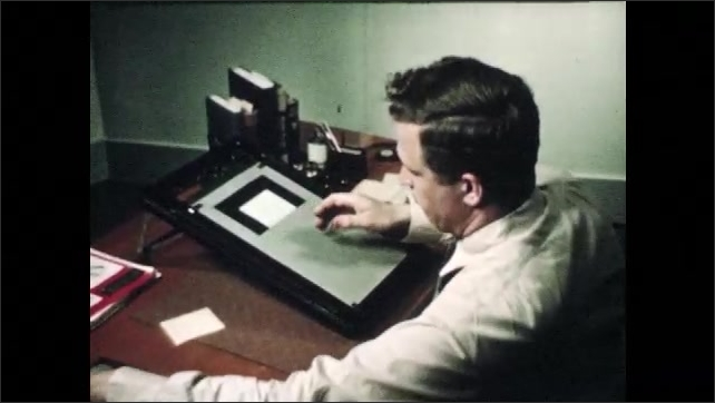 1940s: Man puts book away.  Man sets up lightbox and views slide.