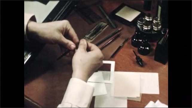 1940s: Man opens bottle of ink and prepares pen.