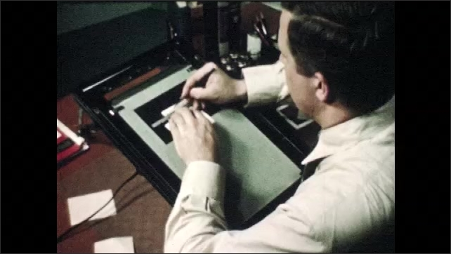 1940s: Man tests pen on piece of paper.  Man uses ruler to trace image on lightbox.