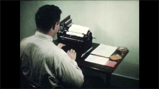 1940s: Man types on typewriter.  Man removes paper and puts aside.