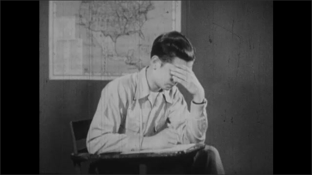 1950s: Young man sits at desk with typewriter and paper and pen. Young man talks. Keys on typewriter. Typewriter types on paper.