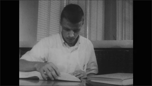 1950s: Row of encyclopedias on shelf in school library. Young man takes encyclopedia off shelf, sits at desk, opens it, reads through, then puts it back on shelf.