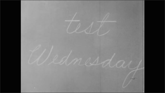 1950s: student talking to teacher after class, teacher telling students test on Wednesday