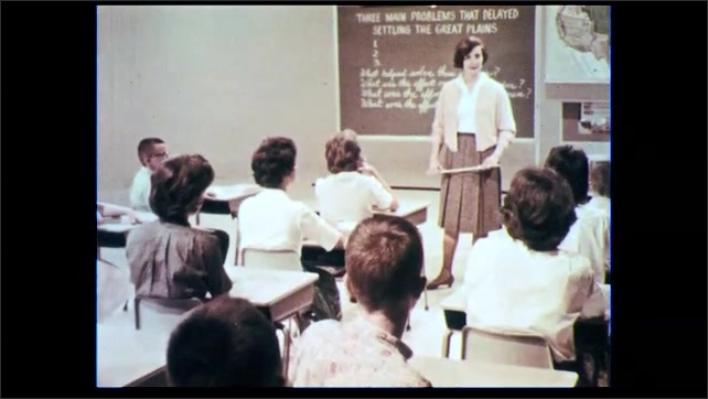 1960s: Woman talking in front of classroom. Close up of woman talking.