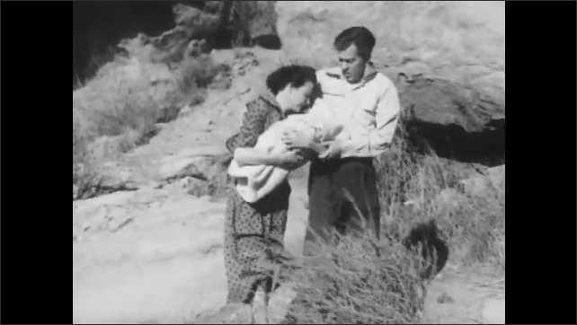 1950s: Couple stand in scrubby wilderness, woman holds baby, they walk uphill against heavy dusty wind, man puts arm around woman, they talk, look worried, man takes baby.