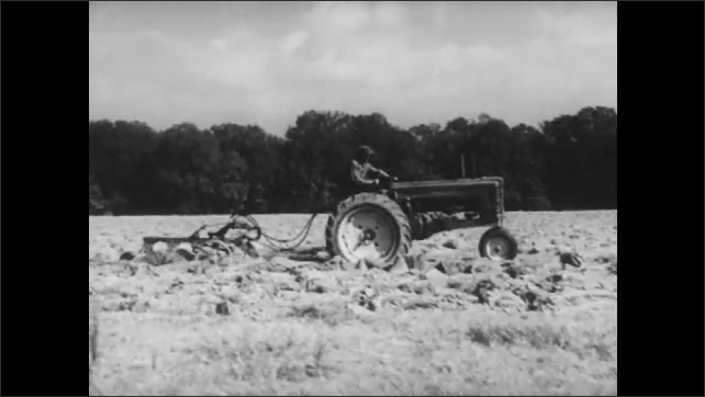 1950s: Agricultural field. Farmer on tractor pulls steel plow across earth, looks back, steers.