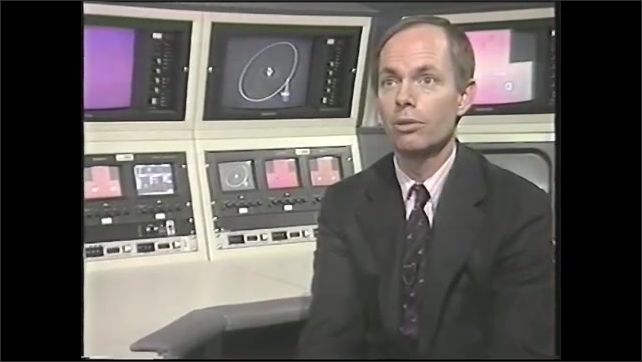 1990s: Scientist makes notes and observations in office. Dr. Peter Stockman  is interviewed in front of bank of monitors.