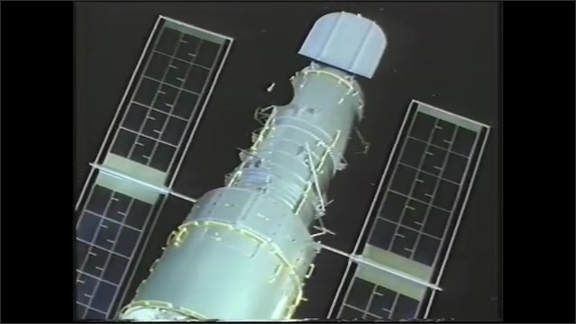 1990s: Animation of Hubble Telescope moves through the sky. Man moves his rolling chair in lab full of computers. Sign reads Space Telescope Operations Control Center in control center.