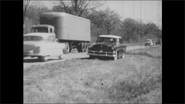 1950s: scared man driving, steering wheel turns quickly, car swerves off road, car stops, driver blows out breath with relief, shakes head