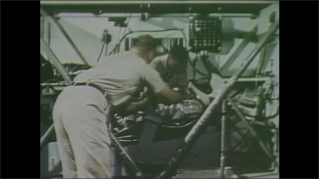 1980s: Man jumps into reclining seat in capsule.  Men strap astronaut into place.  Man sits at control panel.
