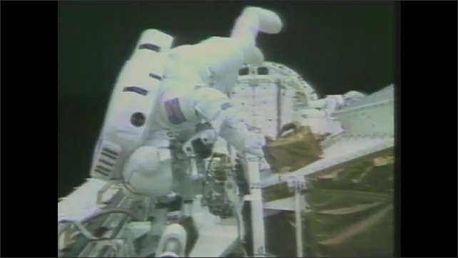 1980s: Astronauts work on outside of space shuttle.  Man holds on to ship.  Man tightens bolt.