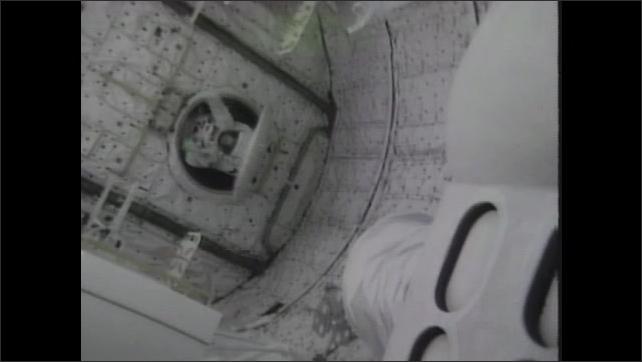 1980s: Men in space suits.  Astronaut comes back through hatch into space shuttle.