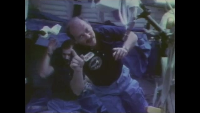 1980s: Astronauts float in cabin.  Man looks at map and turns upside down.  Man points and drifts along.  Man puts a box against his head and pushes off the wall.  Man bounces back and forth.