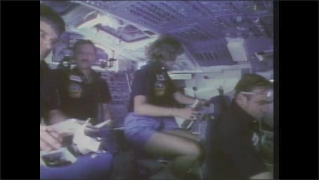 1980s: Astronauts work in cockpit.