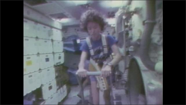 1980s: Men work in cabin of space shuttle.  Man looks out window.  Woman walks on treadmill.