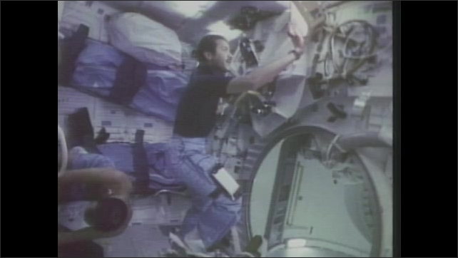 1980s: Men float in space shuttle cabin.  Man shakes object and attaches it to light.  Man looks through camera.