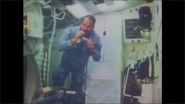 1980s: Astronaut drinks from pouch.  Man floats out of space shuttle cabin.